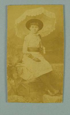 Sepia studio photograph of a young girl in a dress and hat