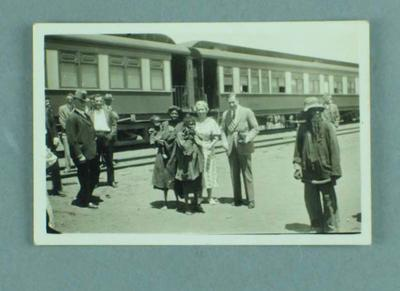 Photograph of a group of people standing near a train