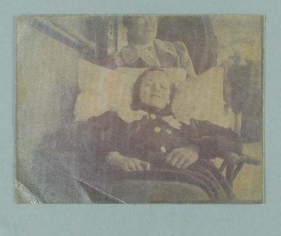 Photograph of a sickly young girl, lying back in a cane chair