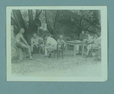 Photograph of a group of people sitting outside underneath some trees, c1951