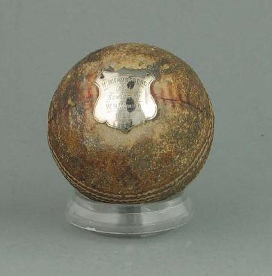 """Cricket ball with silver plaque: """"W. Munro - Bowled W. Armstrong  Ballarat 1924"""""""