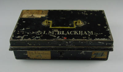 Black cash tin inscribed J. M. Blackham