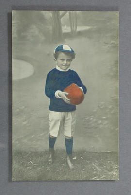 Postcard with image of young boy holding a football, c1914