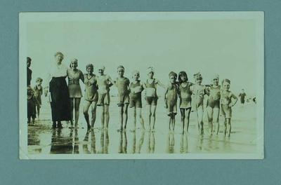 Photograph of a group of girls on beach, all dressed in swimming costumes
