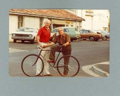 Colour photograph of Rupert Bates and another man with a bicycle  in front of Bates Cycles shop, January 1983.