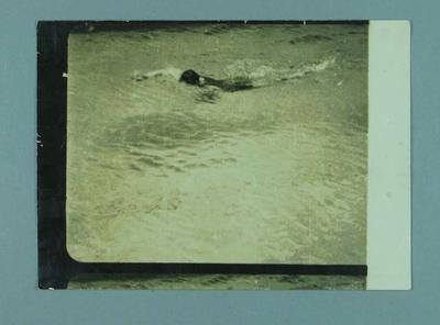 Photograph of a man swimming in a pool