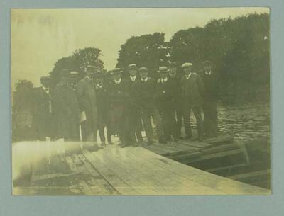 Photograph of fourteen men, standing on a docking platform on a river