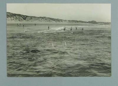 Photograph of a number of people swimming at a beach, all dressed in swimming costumes