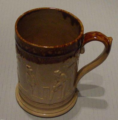 Brown ceramic mug with raised decorations of cricketers Fuller Pilch, Charles Box and William Lillywhite