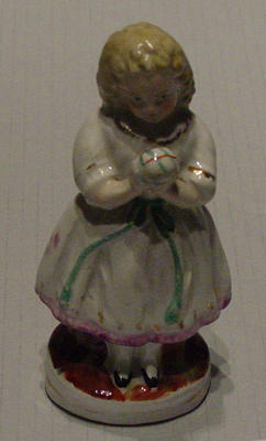 Ceramic Staffordshire figurine of a girl holding a cricket ball