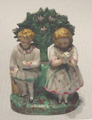 Ceramic Staffordshire figurine of boy and girl with cricket equipment