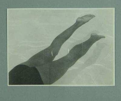 Photograph of a male swimmer demonstrating a kicking technique in a pool