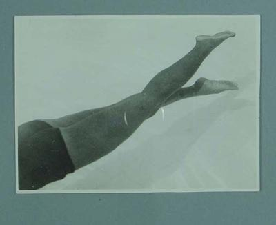 Photograph of a male swimmer, demonstrating a kicking technique in a pool