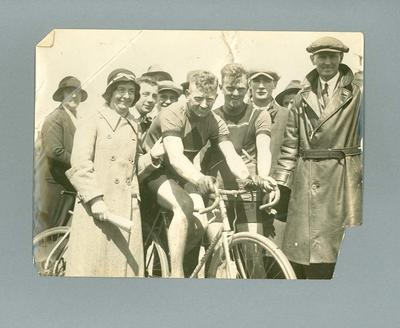 Black and white photograph of Ernie Milliken on his bicycle in a group of people; Photography; 1986.81