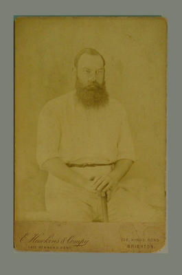 Sepia photographic portrait of W.G. Grace, seated holding a bat.