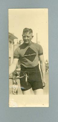 Black and white photograph of Ernie Milliken holding  his bicycle