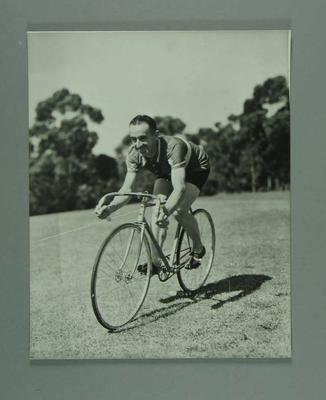Black and white photographic copy, Eric Gibaud on his bicycle