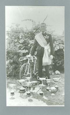 Black and white photographic copy of  original, showing friend of Eric Gibaud beside Eric's bicycle land some of Eric's trophies & sashes