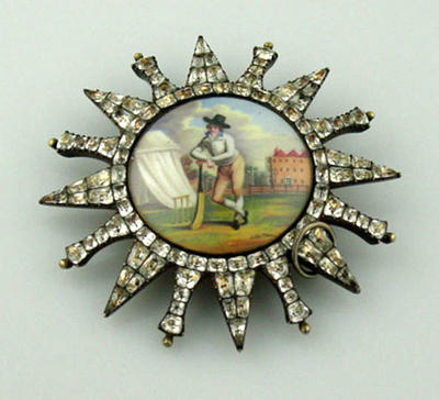 Star or sun-shaped brooch with  image of  a cricketer in the centre