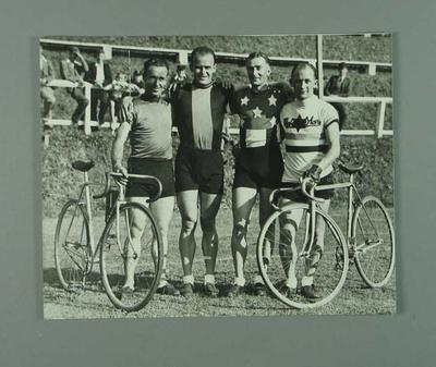Black and white photographic copy showing N. Moritz, H. Turtill , P. Veitch, E. Gibaud holding bicycles during New Zealand Tour
