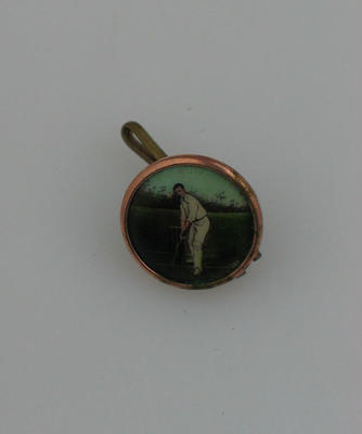 Button with image of cricketer, metal loop at rear