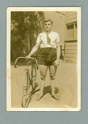 Black and white, sepia toned photograph of a man holding a bicycle - Horice Horder