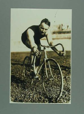 Black and white, sepia toned copy photograph of Bob Spears on Bicycle