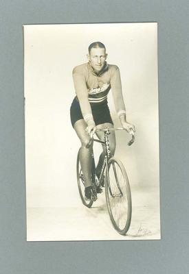 Black & white photograph of Bobbie Pearce riding a bicycle