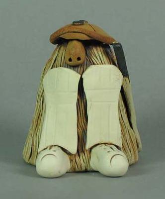 Ceramic figurine of creature in cricket batting attire