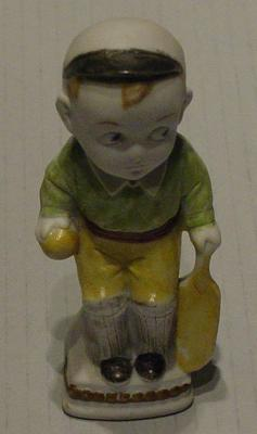 Ceramic figurine of boy with bat and ball