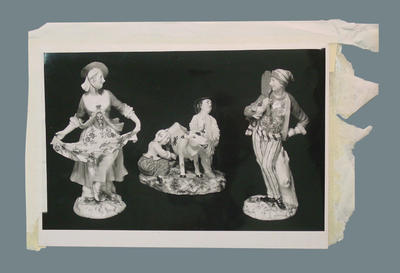 Photograph of three porcelain figurines, one with cricket bat