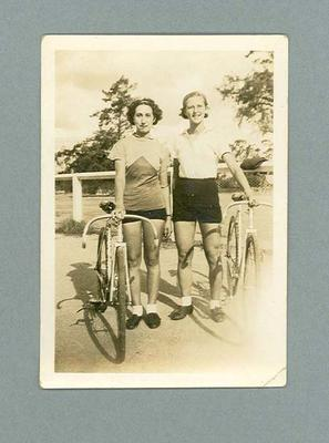 Photograph of two female cyclists with bicycles, c1938