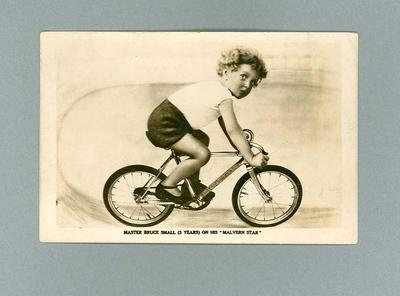 Postcard featuring image of a small child riding a bicycle, c1920s