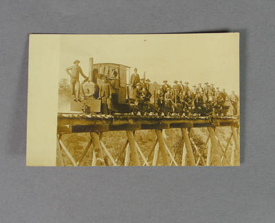 Postcard depicting a group of men, posing around a small gauge steam train, c1910s-20s