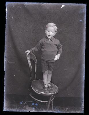 Glass negative, image of young boy standing on a chair