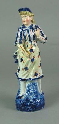 Ceramic Delft-style figurine depicting girl with cricket ball