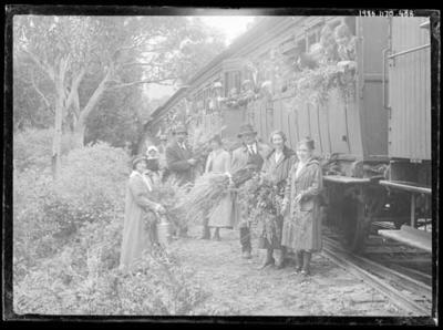Glass negative, image of group standing near train