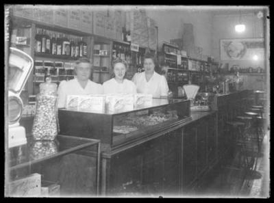 Glass negative, image of three unknown women standing behind the counter of a store