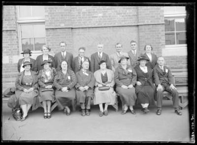 Glass negative, image of group outside brick building
