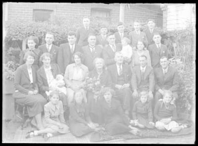 Glass negative, image of large family group outside a house