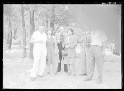 Glass negative, image of small group standing near trees