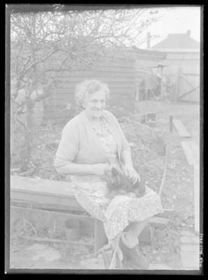 Glass negative, image of unknown woman in a garden with small dog
