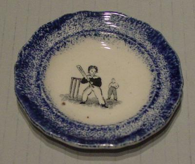 Small ceramic plate with blue border and 2 boys in the centre playing cricket