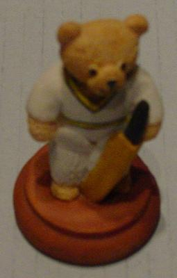 Miniature figure of a bear in cricket whites holding a bat