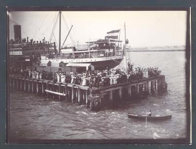 Photograph from Frank Laver's photograph album, view from passenger ship of crowd circa 1900