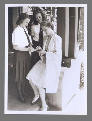 Photograph of Shirley Strickland signing autographs, undated