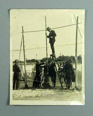 Photograph of officials setting pole vault bar, c1927