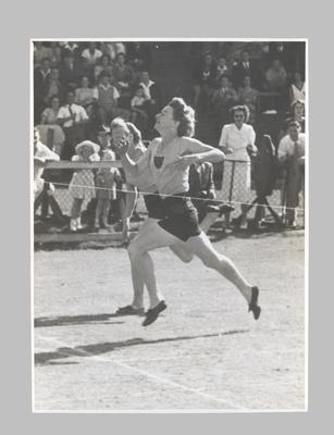 Photograph of Joyce King crossing finish line, 1948 National Championships