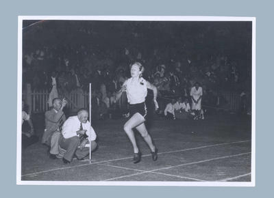 Photograph of Shirley Strickland at the finish line of a running race, c1949