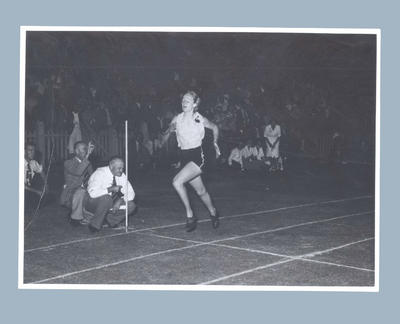 Photograph of Shirley Strickland at the finish line of a running race, c1950